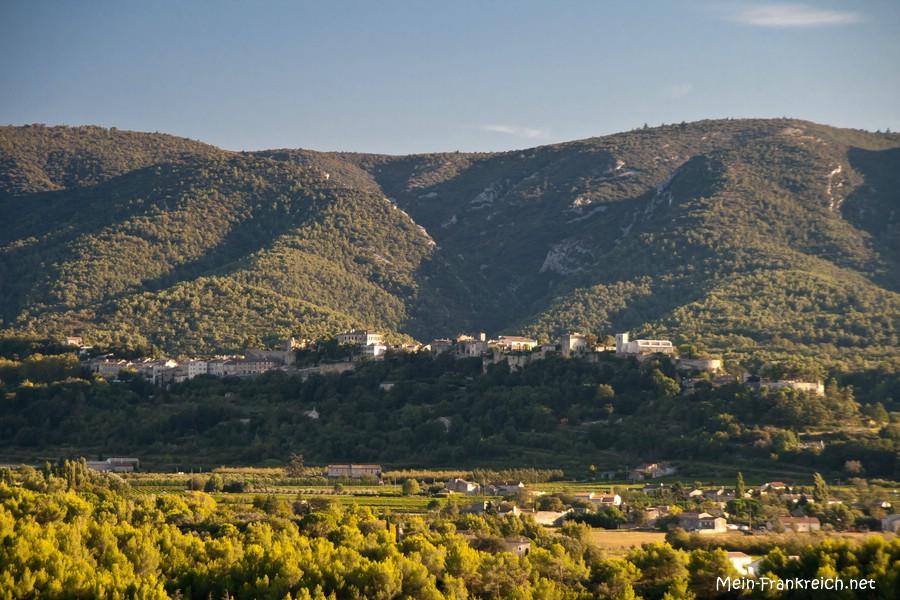 Ausblick von oberhalb des kleinen provenzalischen Dorfes Beaumettes auf die Berge des Luberon und das Dorf Ménerbes im Abendlicht